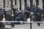 Сотрудники чрезвычайных служб оказывают помощь раненым и пострадавшим в результате стрельбы у Вестминстерского моста в Лондоне