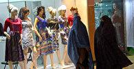Афганские женщины проходят мимо витрины магазина одежды в Герате
