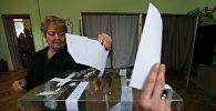 Женщина принимает участие в голосовании в ходе парламентских выборов в Болгарии, в Софии