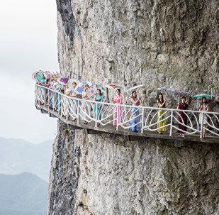 Женщины с зонтиками позируют для группового фото на дорожке вдоль скалы в муниципалитете Чунцин в Китае