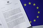 Копия письма британского премьер-министра Терезы Мэй c уведомлением о намерении Великобритании покинуть ЕС рядом с европейским флагом