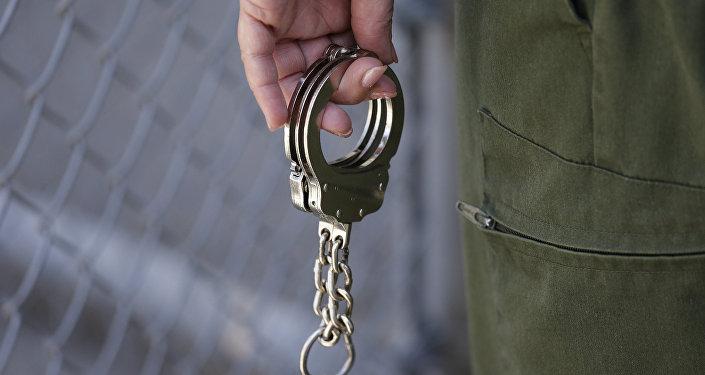 Охранник держит пару наручников