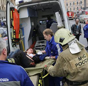 Пострадавшему помогают аварийные службы за пределами станции Технологический институт после взрывов в двух вагонах поезда на станциях метро в Санкт-Петербурге, Россия