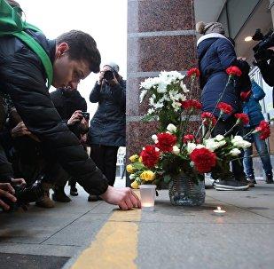 Люди возлагают цветы и зажигают свечи у входа на станцию метро Спасская в память о погибших в результате взрыва в метрополитене Санкт-Петербурга