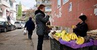 Женщина покупает овощи и фрукты у уличного торговца в центре грузинской столицы
