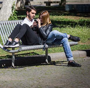 Парень и девушка на скамейке в парке