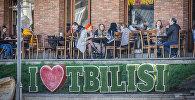 Посетители кафе сидят за столиками на улице