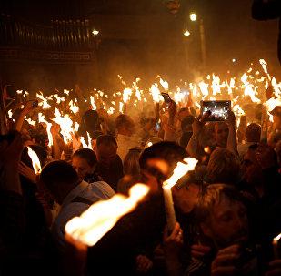 მორწმუნეებს წმინდა ცეცხლით ანთებული სანთლები უჭირავთ იერუსალიმში მაცხოვრის საფლავთან