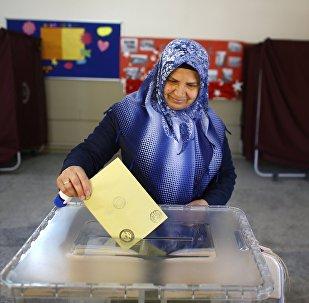 Женщина бросает бюллетень в урну во время референдума в городе Измир, Турция