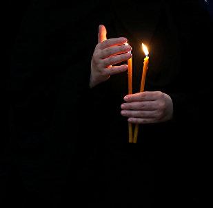 Монахиня держит зажженную свечу во время праздничной Пасхальной службы в Кафедральном соборе Святой Троицы Самеба