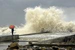 Человек с берега смотрит на шторм на Черном море