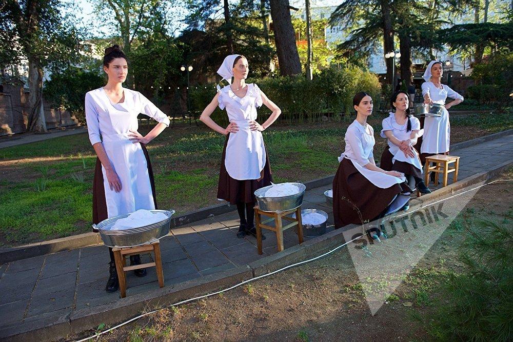 Модели участвуют в постановке сцены с танцами прачек из киномюзикла Мелодии Верийского квартала на открытии Тбилисской Недели моды
