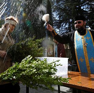 Священник благословляет прихожан с вербой в ходе воскресной службы