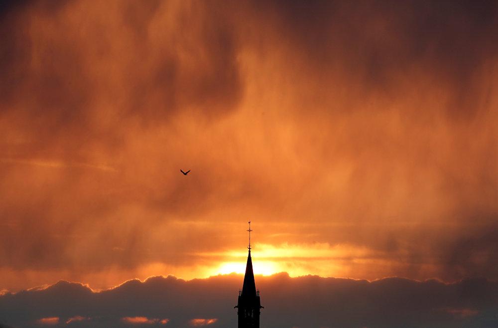 Виноградники уже пошли в рост после зимы, когда вновь ударили холода. На фото - дождь и облака на закате над церковью в Шабли, Франция