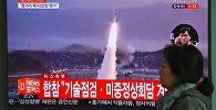 Женщина проходит мимо телевизионного экрана, показывающего видеозапись запуска ракеты Северной Кореей, на железнодорожной станции в Сеуле