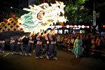 Буддийские верующие с гигантским драконообразным фонарем во время парада в честь наступающего дня рождения Будды в Сеуле, Южная Корея