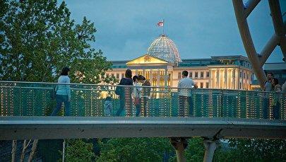 Туристы идут по пешеходному Мосту Мира на фоне президентского дворца в центре Тбилиси