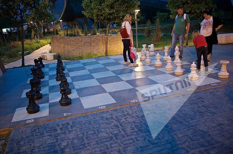Туристы вечером в Парке Рике играют в шахматы