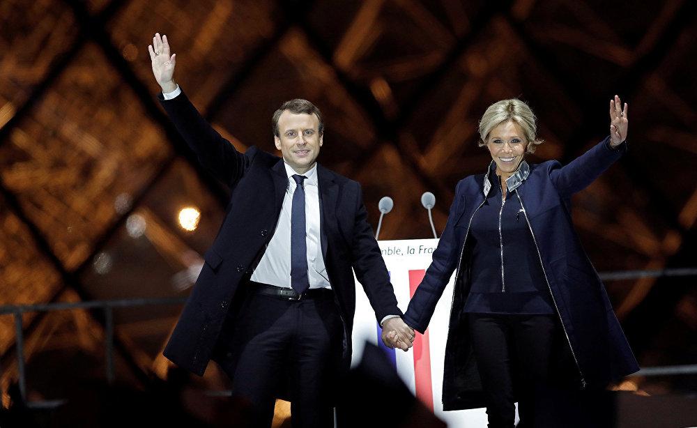 Избранный президент Франции Эммануэль Макрон со своей супругой Брижит Макрон обращается к избирателям на праздничном митинге у Лувра, Париж
