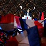 Избранный президент Франции Эммануэль Макрон приветствует своих избирателей на праздничном митинге у Лувра, Париж