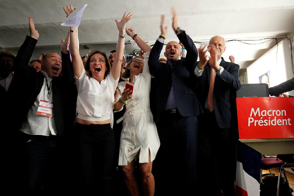 В избирательном штабе Эммануэля Макрона в Марселе его сторонники радуются после объявления предварительных итогов второго тура президентских выборов во Франции