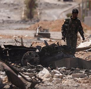 Сирийские демократические силы проходят по поврежденной улице в городе Табха, после захвата ее у исламских боевиков