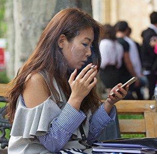 Девушка с сигаретой и смартфоном в руках