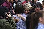 Люди обнимаются после эвакуации из торгового центра Arndale в Манчестере