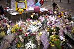 Женщина в центре Манчестера возлагает цветы к мемориалу жертв террористического акта на стадионе Манчестер Арена