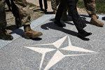Люди идут по плацу с символикой НАТО