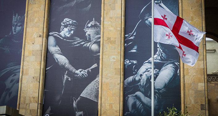 Флаг Грузии на фоне иллюстраций к поэме Шота Руставели Витязь в тигровой шкуре, расположенных на здании Парламента Грузии