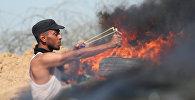 Палестинский протестующий стреляет камнями из рогатки в сторону израильских солдат во время столкновений недалеко от границы между Израилем и Сектором Газа