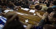 Родственники коптских христиан, погибших в Египте во время нападения группы вооруженных лиц на автобус, оплакивают своих близких