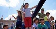 Дети на самоходной артиллерийской установке Dana фотографируются на память во время выставки вооружений в День Независимости Грузии
