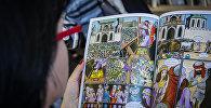 Девушка рассматривает комикс по мотивам поэмы Витязь в тигровой шкуре
