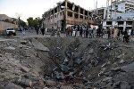 Афганские силовики и жители стоят возле воронки, оставленной в результате взрыва заминированного грузовика в Кабуле