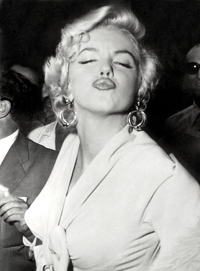 Американская актриса Мэрилин Монро позирует перед фотографами, 1954