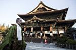 Японский монах покидает буддийский храм Зенкю после утренних молитв в Нагано