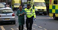 Полицейский помогает эвакуировать местного жителя недалеко от места серьезного пожара в жилом доме в Западном Лондоне, Великобритания