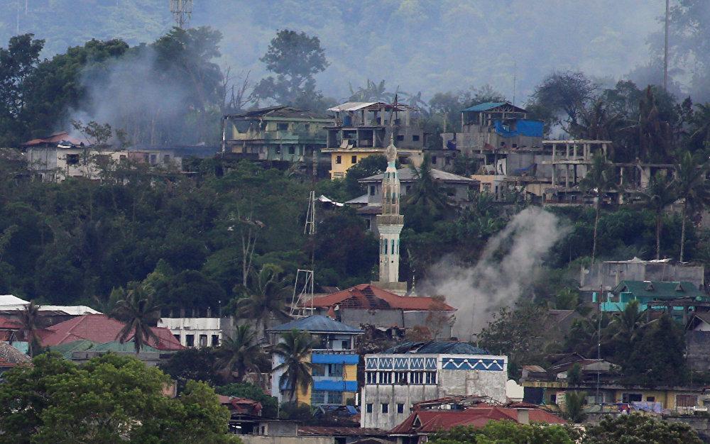 Дым поднимается над горящими зданиями во время атаки правительственных войск против группировок исламистов из группы Маута, захвативших большую часть города Марави