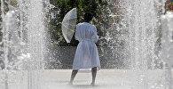 Женщина спасается от летнего солнца под брызгами фонтана в середине жаркого июньского дня в Париже, Франция