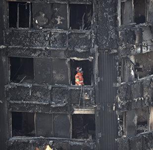 Один из сотрудников службы спасения работает на месте пожара в многоэтажном жилом доме в Лондоне