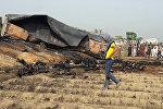 Местные жители смотрят на сожженные тела после того, как бензовоз загорелся после аварии на шоссе недалеко от города Ахмедпур, примерно в 670 километрах от Исламабада