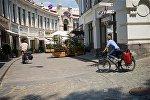 Туристы на велосипедах на улице Шардена в историческом центре Тбилиси