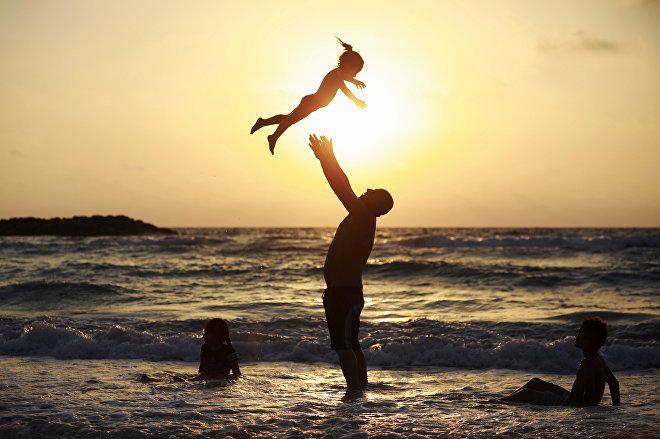 Мужчина играет со своей дочерью у берега Средиземного моря в Ашкелоне, Израиль