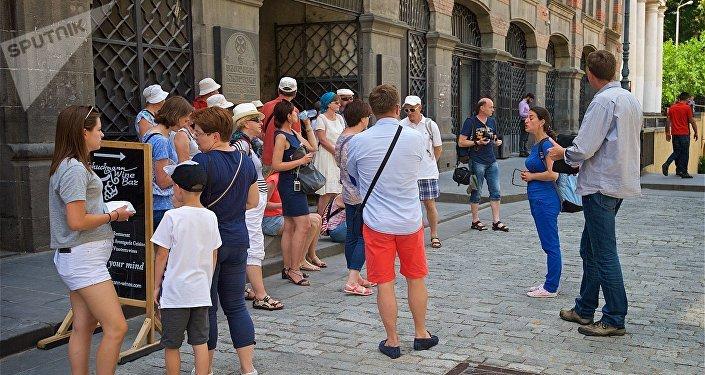 Туристы у здания духовной семинарии в историческом центре Тбилиси, рядом с храмом Сиони