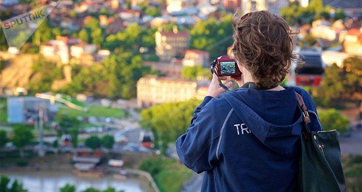 Туристка фотографирует Тбилиси на смартфон со смотровой площадки