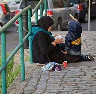 Нищенка с ребенком просит милостыню у крепости Нарикала