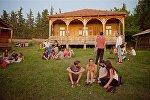 Люди отдыхают, сидя на земле на территории Этнографического музея летним вечером в Тбилиси