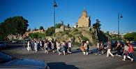 Группа туристов переходит дорогу в центре Тбилиси у Метехского моста